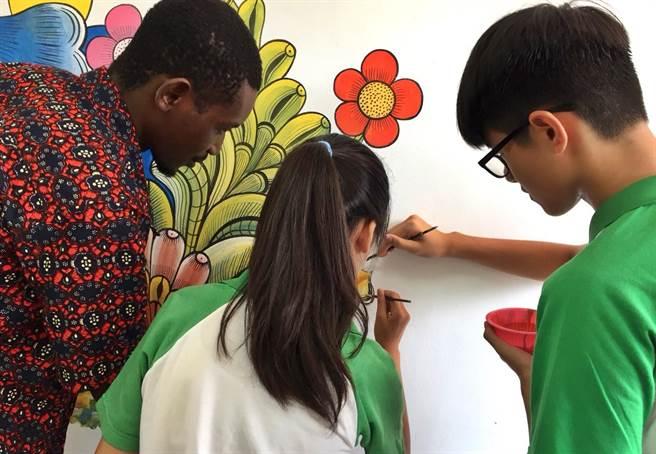 ▲非洲坦尚尼亞的藝術家Kipara指導學生們如何用色以及用筆觸和構圖進行彩繪。(楊樹煌攝)