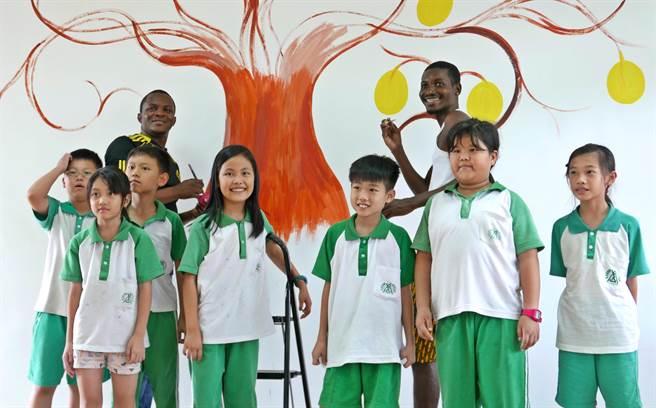 ▲來自非洲坦尚尼亞Mzuguno家族的藝術家Kipara與虎山小朋友為圖書室大牆進行的彩繪工程。(楊樹煌攝)