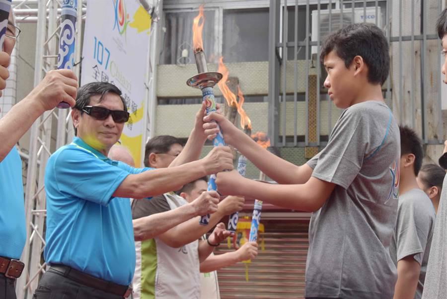 嘉義市長涂醒哲把點燃的聖火交到聖火隊手中。(呂妍庭攝)