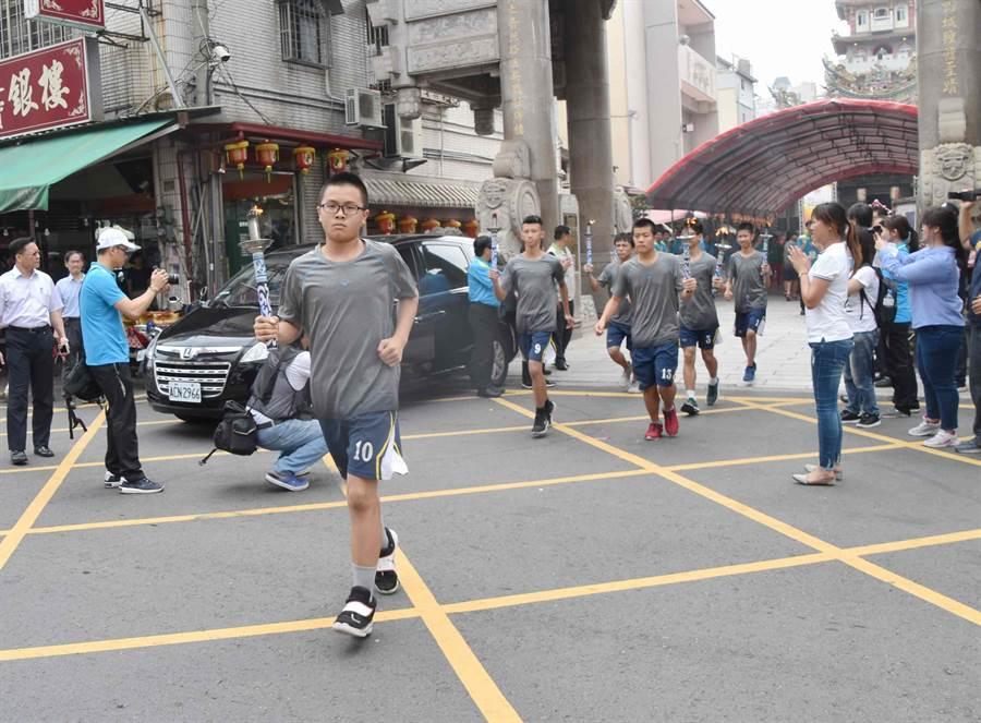運動員接過聖火後,在警車開道指揮下,以一隊傳一隊接力方式陸續接棒。(呂妍庭攝)