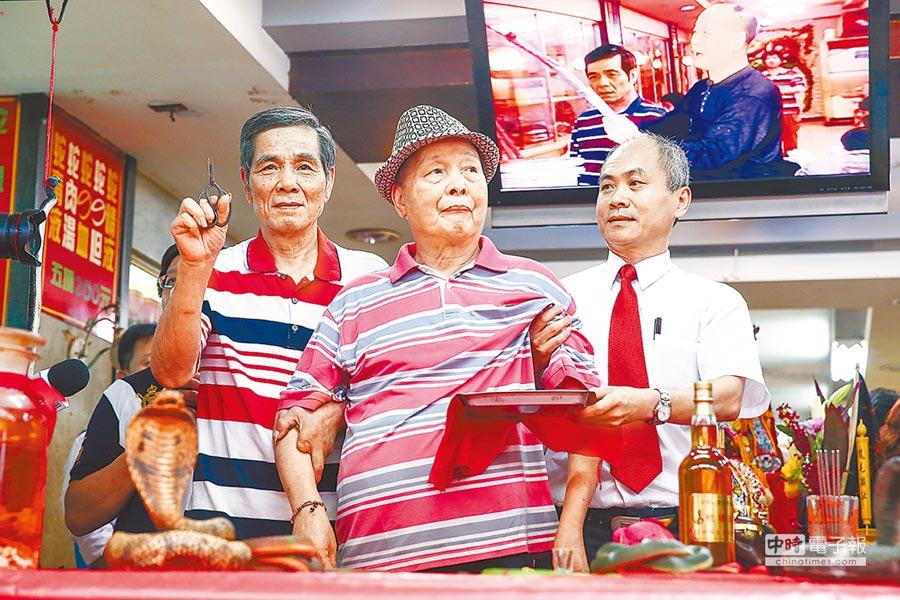 亞洲毒蛇研究所21日正式熄燈,最後一代弄蛇人洪丁福(左)與郭家兩代老闆郭來貢(中)一同為殺蛇剪封刀。(鄧博仁攝)