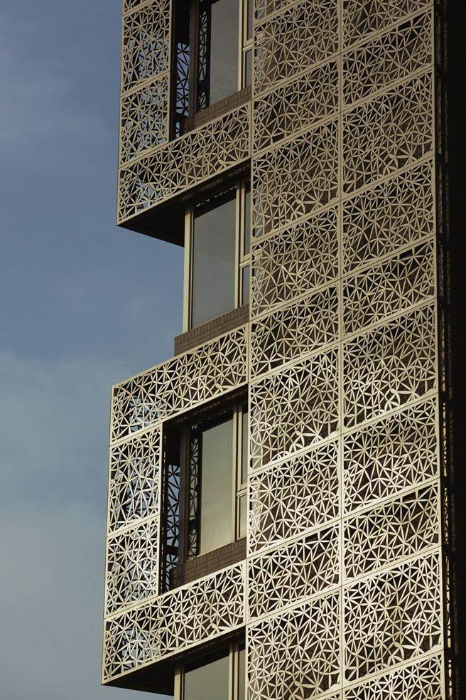 外觀採雙層外牆(Double Skin)工法,透過花朵意象及建材設計,採不受氣候影響的奈米氟碳金屬鋁板與石材,達到環保及節能之效。(圖/三本建設提供)