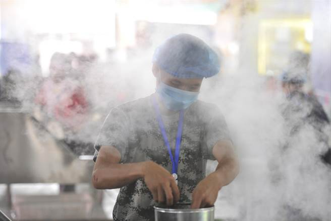 雲南省普洱市舉辦的第15屆中國普洱茶節,傳統普洱茶製作工藝亮相,蒸茶工人展現手藝,吸引民眾圍觀。(圖/中新社)