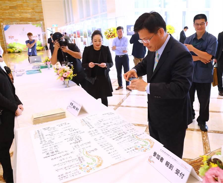 台中市長林佳龍1日出席「第11屆台日觀光高峰論壇」,特別用手機拍下簽名簿,除了重視出席賓客,也紀錄觀光與榮耀的「影」響力。(盧金足攝)