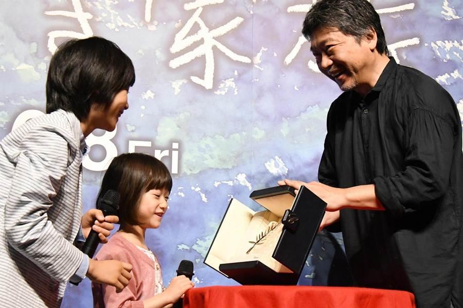 導演是枝裕和(右)開心地對童星城檜吏(左)、佐佐木光結(中)秀出金棕櫚獎座。(采昌提供)