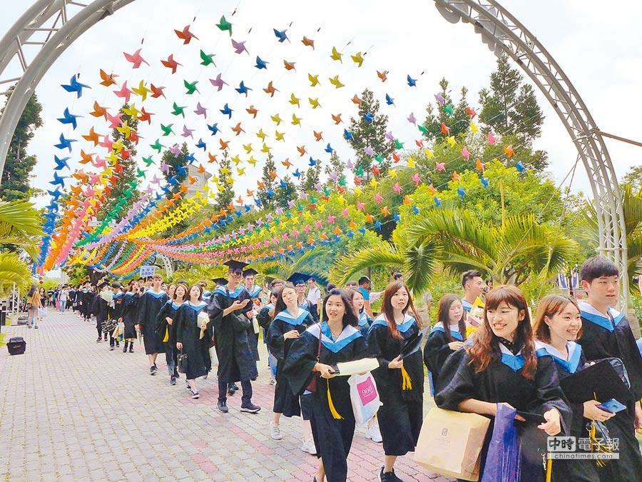 朝陽科大畢業生走過以5000個紙風車編織成的捕夢網下方,盼勇於追求自己的未來。(林欣儀攝)