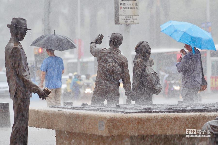 中央氣象局表示,受低壓帶影響,13至16日西南風增強並持續帶來南方水氣,應慎防局部大雨。台北市10日下午降下大雨,街頭民眾撐傘擋雨。(中央社)