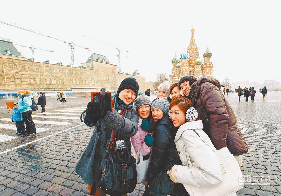 中俄民間旅遊日益活躍,香港大學生在俄羅斯莫斯科紅場拍照留念。(新華社)