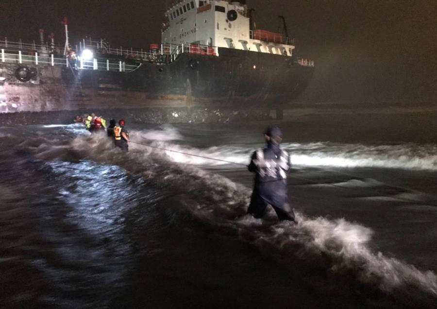 淀泊高雄鳳鼻頭漁港外海的斐濟籍油輪「勝利者19號(WINNER 19)」(中)14日晚間遭強風大雨侵襲導致流錨,擱淺在林園中坑門出水口北方0.2浬沙灘,船上共有14名印度籍船員,海巡和消防人員在船首掛起繩梯,風雨中協助14名船員涉水上岸,全數獲救。(翻攝畫面)