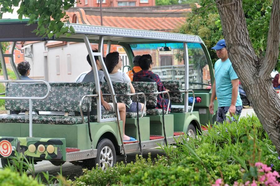 遊客乘坐電瓶車環湖觀賞比賽,十分悠閒自在。(李金生攝)