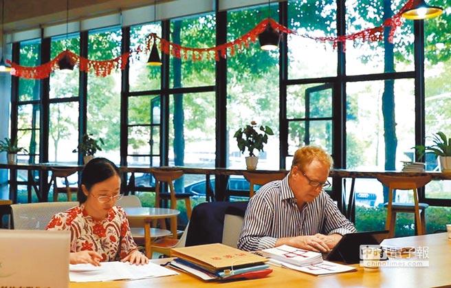 在大陸職場的外國人似乎愈來愈不吃香了。圖為一位英國人(右)在武漢光谷生物城的辦公室內工作。(新華社資料照片)