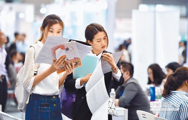 4月14日,國際人才交流大會在深圳舉辦,求職者在海歸人才招聘會上查看企業資料。(新華社)