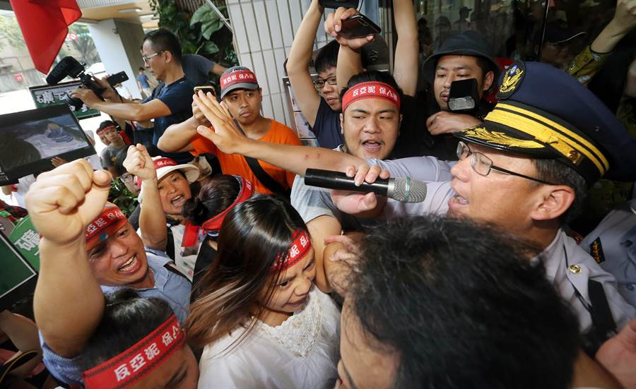 亞泥股東會26日舉行,環保及自救會等團體在場外陳情抗議,在試圖衝入會場時與警方爆發推擠。(范揚光攝)