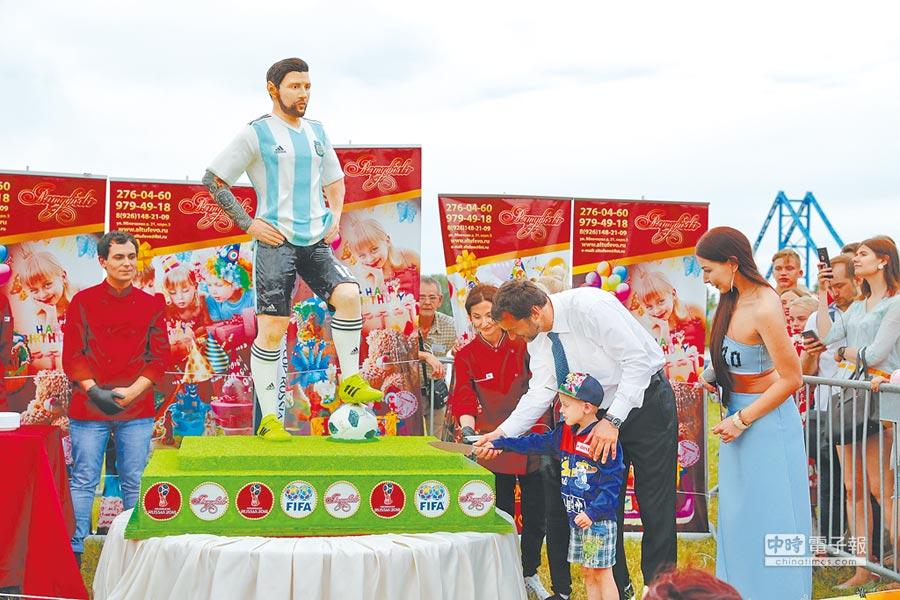 俄羅斯首都莫斯科近郊的布隆尼奇鎮,是阿根廷這次世足賽訓練基地所在,甜點店把要送給梅西的生日蛋糕送到這裡,鎮長協助一名小男孩切蛋糕。(美聯社)