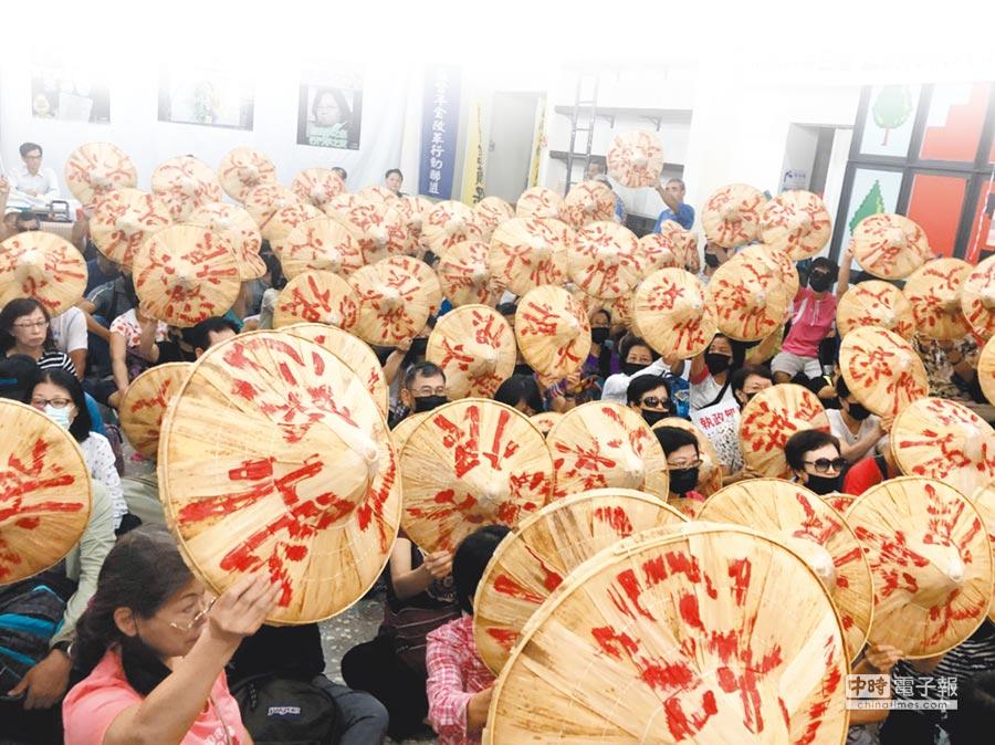 監督年金改革行動聯盟29日記者會中,群眾高舉寫著「恨怒火」3個字的斗笠,表達內心憤怒。(監督年金改革行動聯盟提供)
