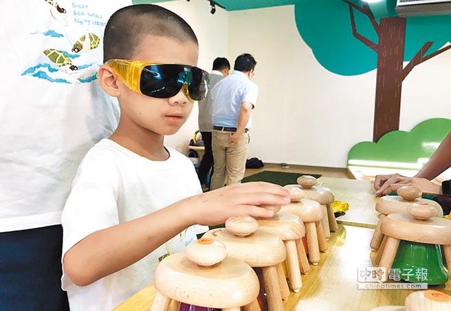 新北市圖鶯歌分館昨日舉辦視障體驗活動,小朋友戴上視障體驗眼鏡玩起手拍鈴。(陳俊雄攝)