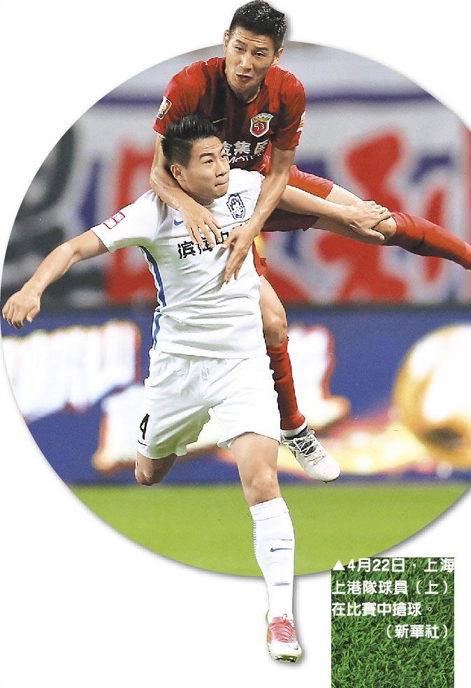 4月22日,上海上港隊球員(上)在比賽中搶球。(新華社)