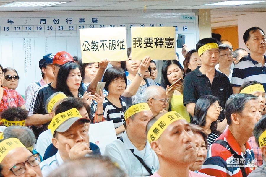 基層退休軍公教警消人員手持「我要釋憲」標語,抗議政府年改手段粗糙違法。(本報系資料照片)