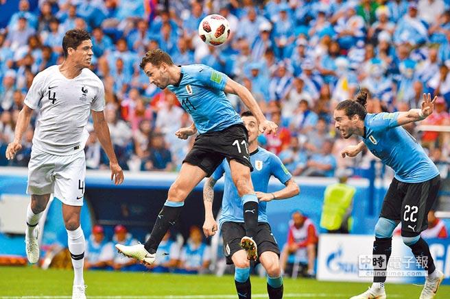 法國後衛佛蘭(左)在第40分鐘趁自由球攻擊,以頭槌率先頂開烏拉圭大門。(法新社)