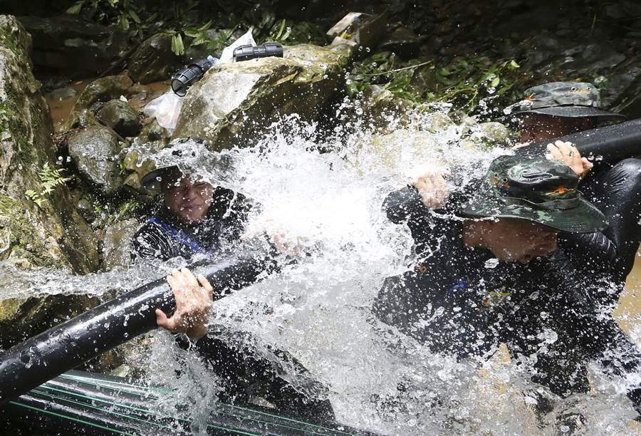 隨著雨季即將降臨,泰國與國際救援人員正與時間賽跑,設法救出受困的13名少年足球隊員與教練,圖為泰國軍人7日試圖安裝更多水管,加速將積水導流出洞外的畫面。(美聯社)