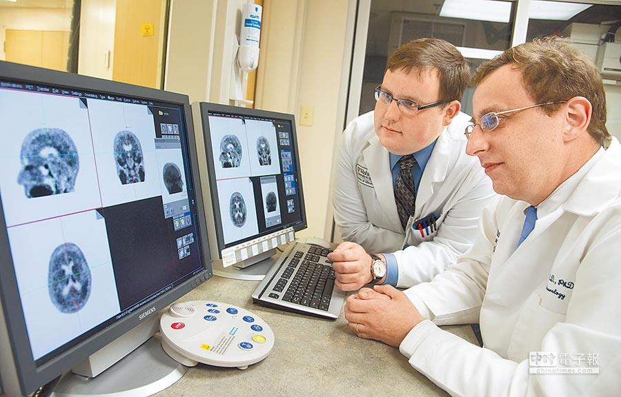 美國華盛頓大學神經內科研究人員觀察阿茲海默症患者的腦部正電子掃描結果。(美聯社)