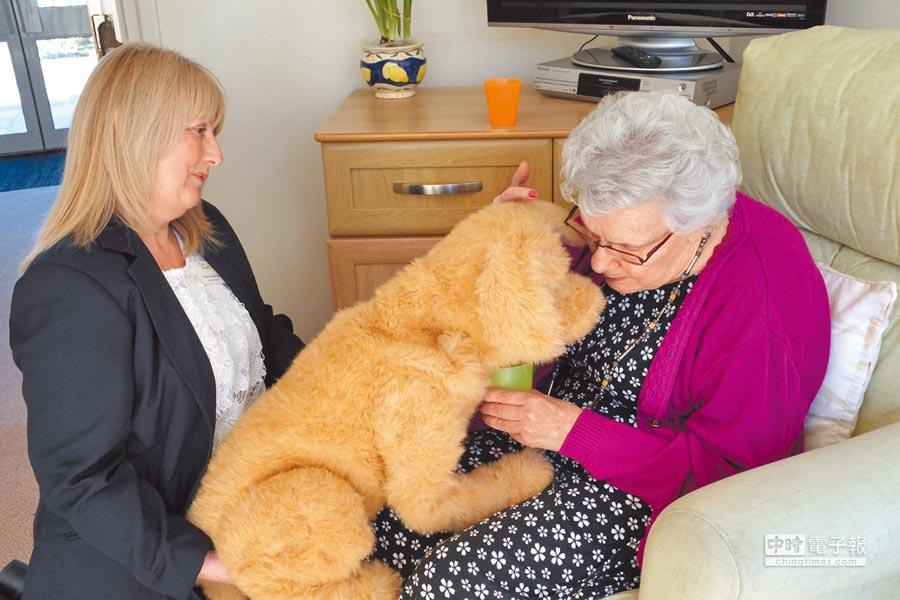 英國73歲女士布魯克(右)對著機器狗「餅乾」說話。這隻機器狗能與失智症老人患者互動,喚起他們的塵封記憶,並誘發他們與照護者對話,深受病患歡迎。(路透)