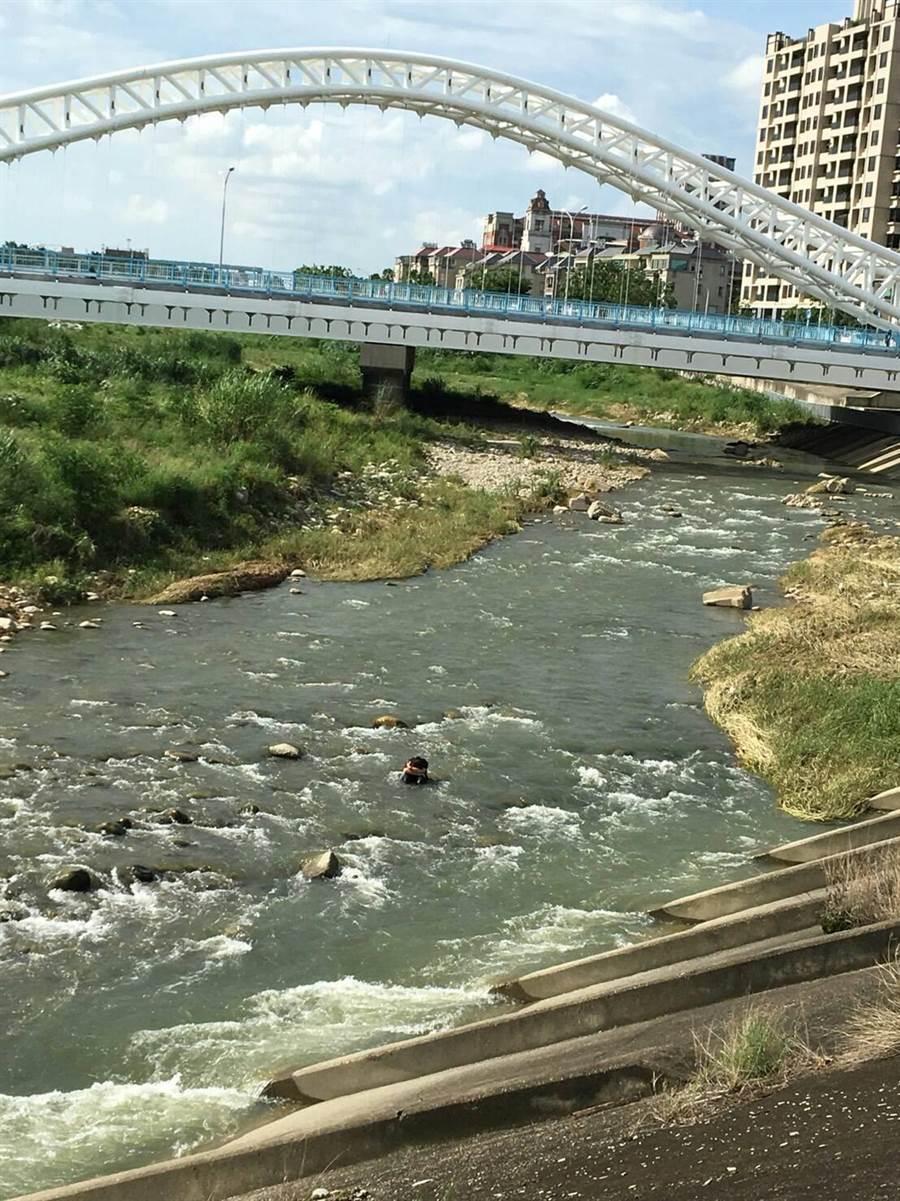 警方在旱溪東路與松竹五路口的旱溪橋下一顆大石發現蘇女坐在大石頭上差點被沖走,即刻把人救起。(張妍溱翻攝)