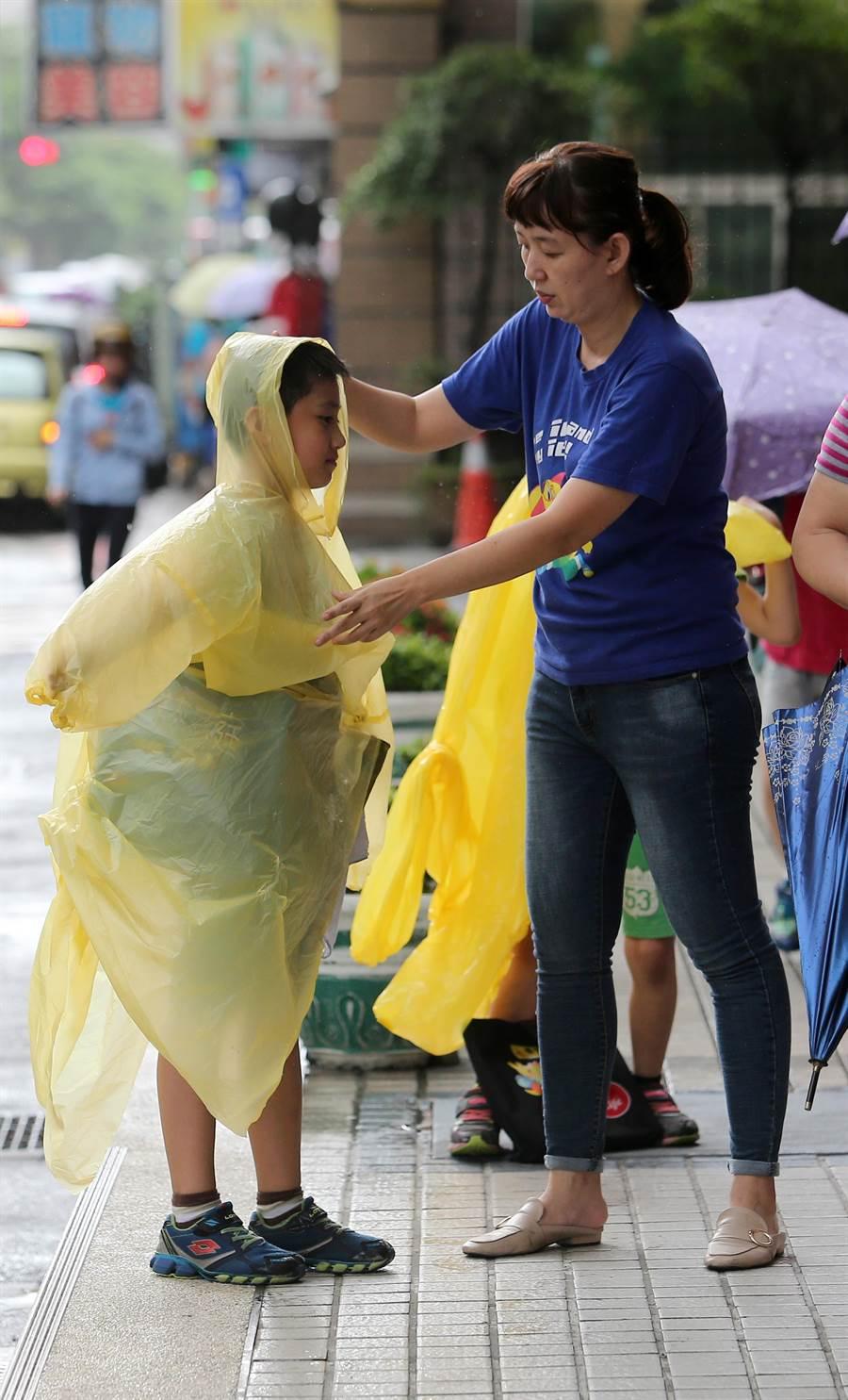 安親班老師細心地幫孩童穿上輕便雨衣。(黃世麒攝)
