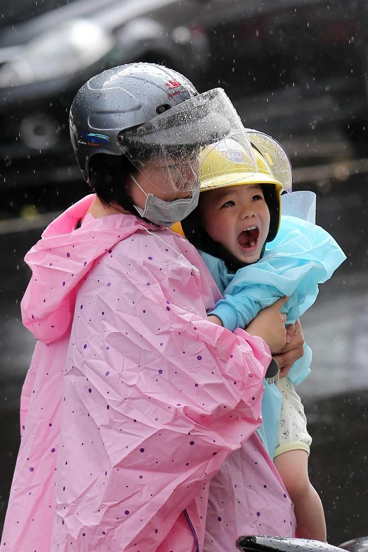 家長趕在風雨不大之際接孩童返家。(黃世麒攝)