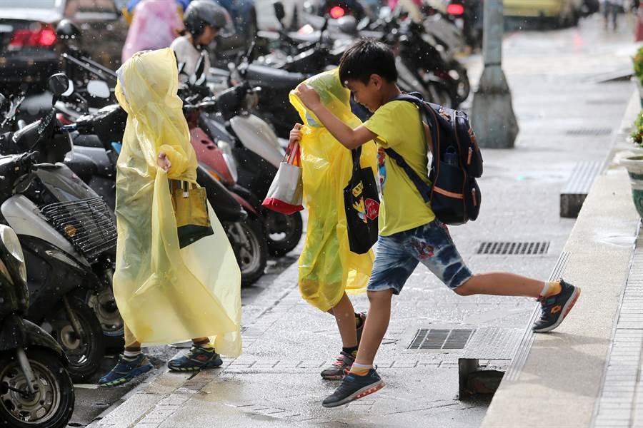 安親班4點下課,孩童趁著風雨不大趕緊返家。(黃世麒攝)
