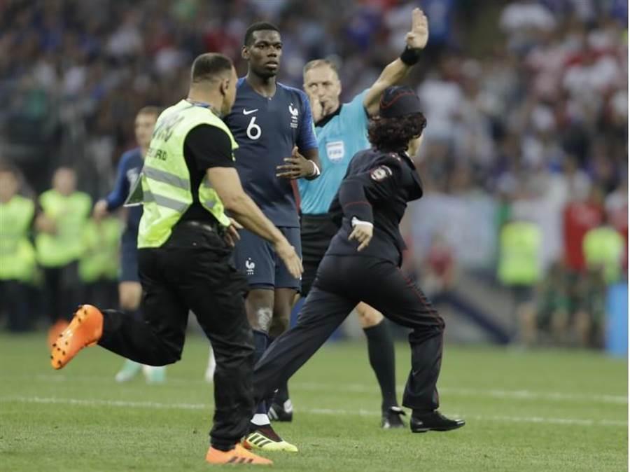 俄羅斯世足賽冠軍賽下半場,有球迷(前右)衝進場亂入,龐克樂團「暴動小貓」坦言是他們所為。(美聯社)