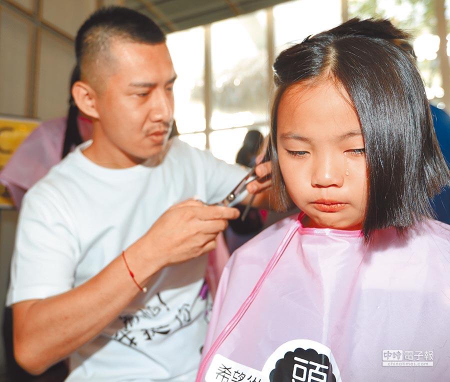 癌症希望基金會舉辦第四屆百人捐髮活動15日登場,一位年僅6歲小朋友響應捐髮,當設計師剪下長髮時,眼淚不自主從眼眶滑下。(陳怡誠攝)
