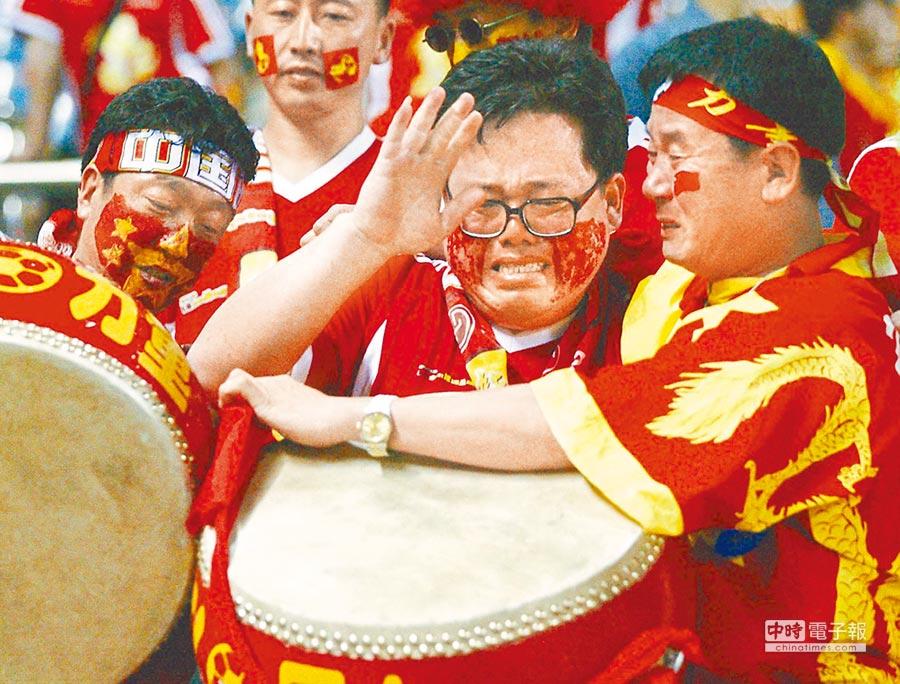 大陸瘋世界盃,球迷觀戰情緒激動。圖為2002年日韓世界盃,中國隊以0比4敗於巴西隊,大陸球迷在看台痛哭流涕。(新華社資料照片)