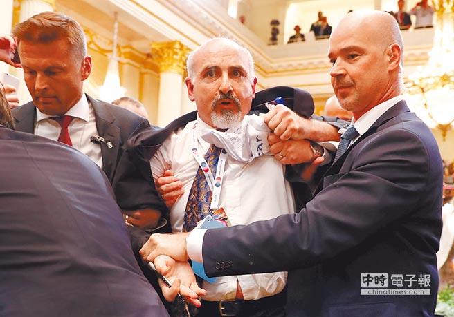 普普會後的記者會開始前,一名男子因不明原因,被安全人員架出場。(路透)