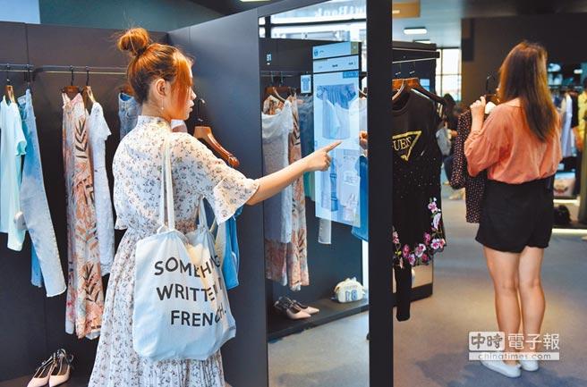 7月4日,阿里巴巴在香港理工大學推出時尚新零售概念店,體驗者在概念店裡體驗人工智慧選購衣服的流程。(中新社)