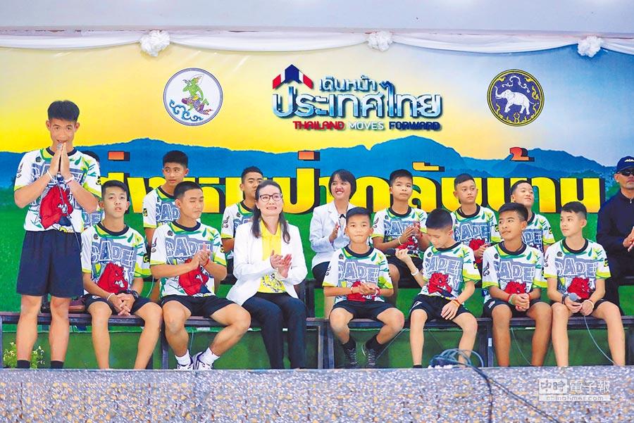 受困洞穴的泰國「野豬」少年足球隊12名小將和教練(左一站立者),18日出院並首度面對媒體。其中一些隊員承諾以後要加入海豹部隊,向罹難和救援他們的海豹隊員致敬。(路透)