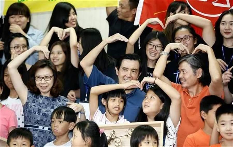 去年彰化家扶二林「新台灣人小學堂」相見歡活動,馬英九一度伸手想和金溥聰「合體」比愛心,不過,金當時已擺好姿勢,馬發現後只好趕緊將放下的手舉起。(資料照片,張鎧乙攝)