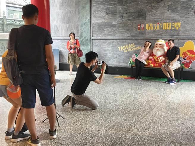 日月潭文武廟「月老寒拾殿」前Q版月老,常吸引年輕人拍照打卡。(沈揮勝攝)