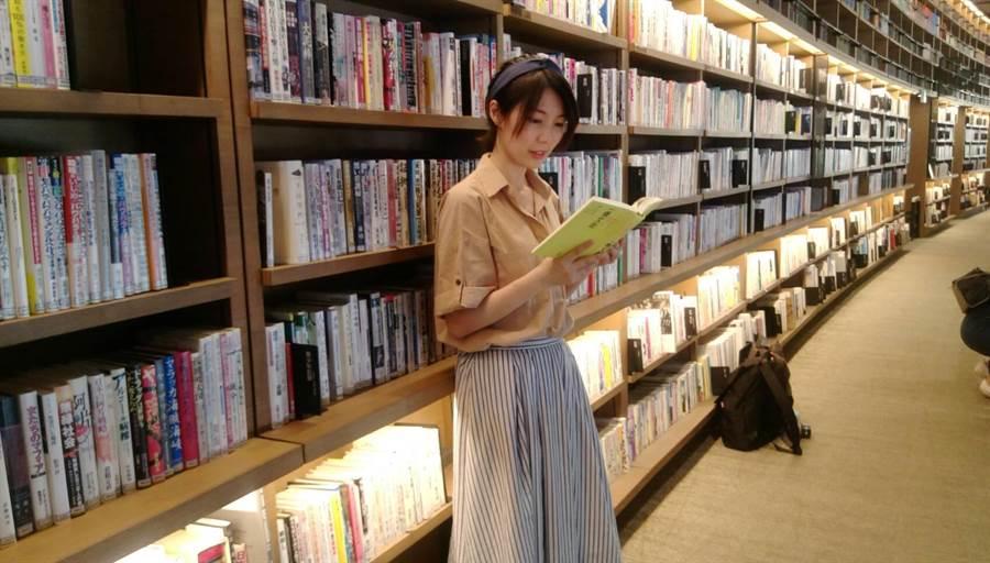 二樓弧形長廊滿牆的書任選。圖中客串模特兒的是經營「文字行旅」的知名部落客艾莉莎。(張佩芬攝)