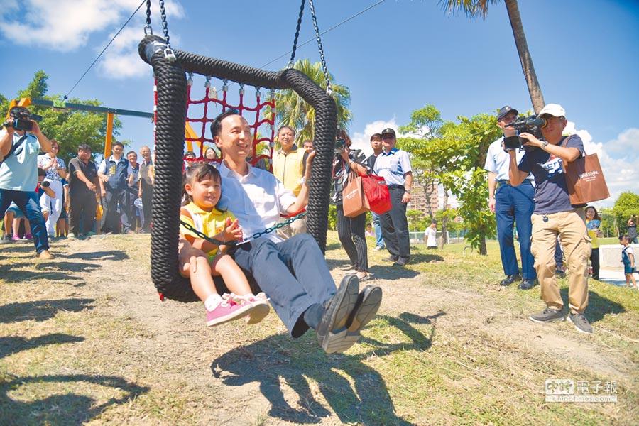新北市長朱立倫表示有信心執政縣市過半。圖為朱立倫與兒童體驗滑索遊具。(譚宇哲翻攝)