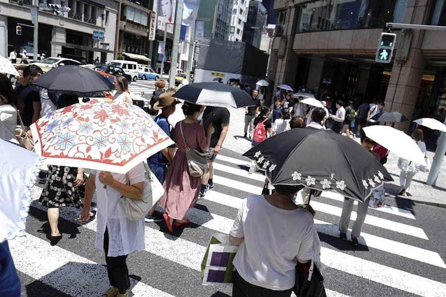 日本遭到10來最嚴重的熱浪侵襲,7月因中暑而死亡人數已破300人。圖為東京街頭民眾撐傘遮蔽烈日。(圖/美聯社)