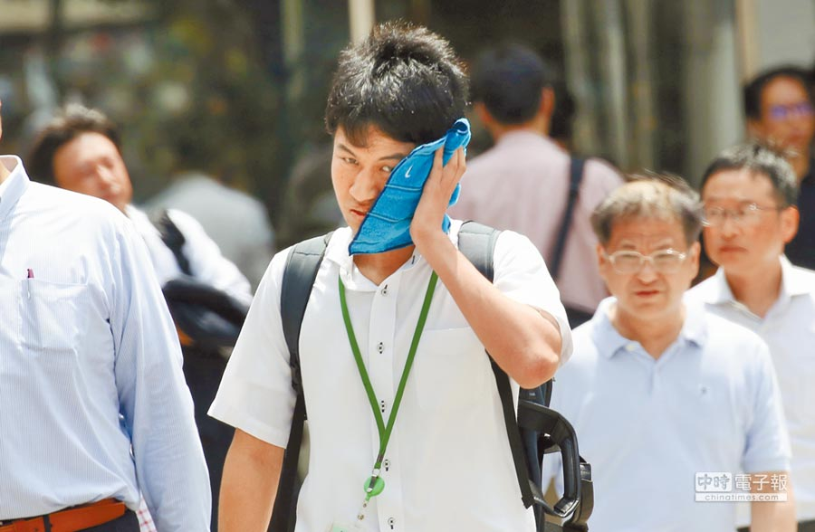 今夏北半球氣溫屢創新高。日本政府昨日指出,近3個月全國中暑送醫逾5萬7千人、死亡125人。圖為東京街頭一名男性難耐酷熱地擦汗。(美聯社)