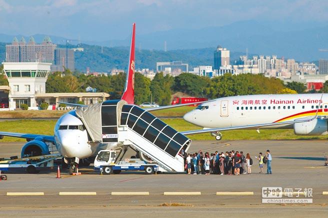 圖為桃園機場旅客搭乘接駁車到接駁坪上飛機。(陳麒全攝)