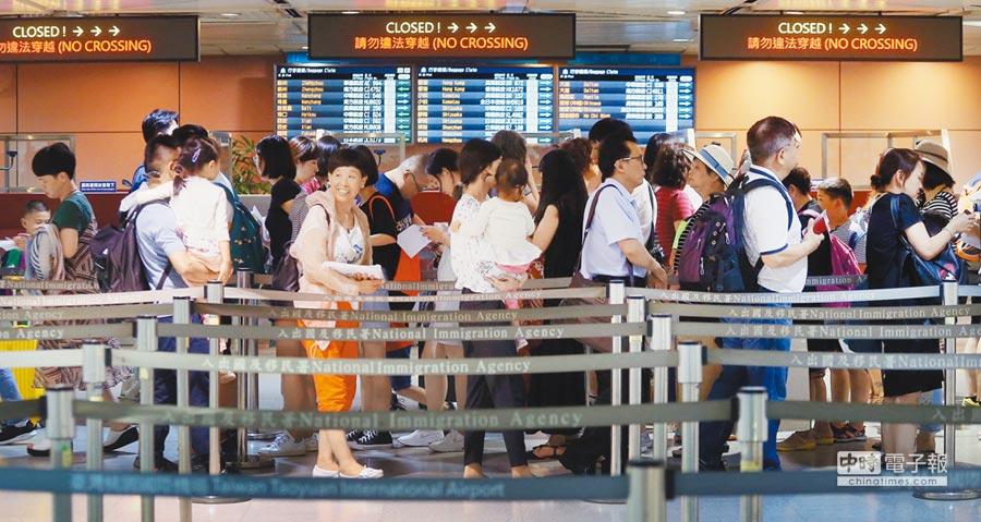 旅客在桃園機場第二航廈排隊入境。(本報系資料照片)