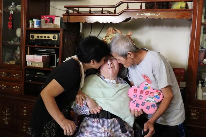 莊爸、莊媽親吻愛女莊嘉慧臉頰。(王文吉攝)