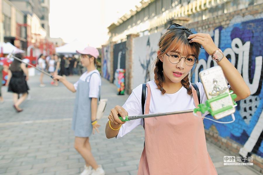 山西太原網紅用手機直播青年創意市集現場。(中新社資料照片)