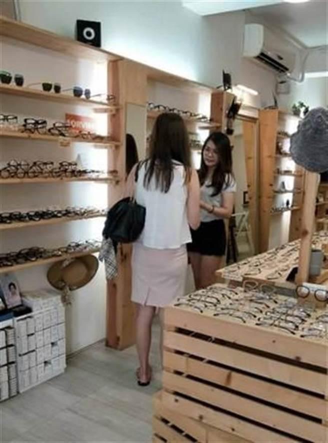 黃羽芊為店裡客戶介紹眼鏡。
