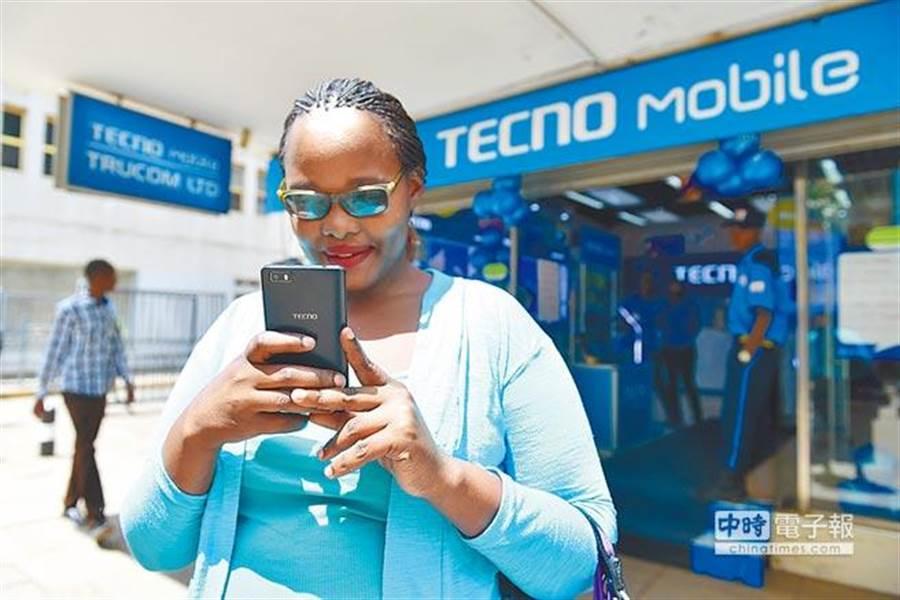 在肯亞首都內羅畢,一名女子拿著傳音手機從傳音專賣店前走過。(新華社資料照片)