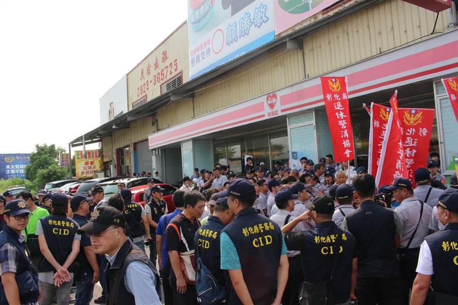 近10名彰化縣退休警消協會的成員,拿著協會的色旗幟, 表達不滿政府大砍退休金的心聲。(吳敏菁攝)