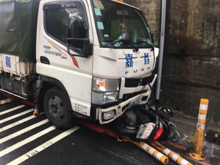 黄姓机车骑士遭爆胎失控的汽车撞进路过货车底盘,命危送医抢救中。(吴岳修翻摄)